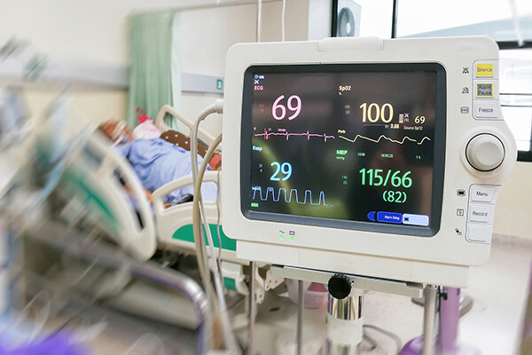 Heart monitor in a hospital room, a patient in a hospital bed behind it.