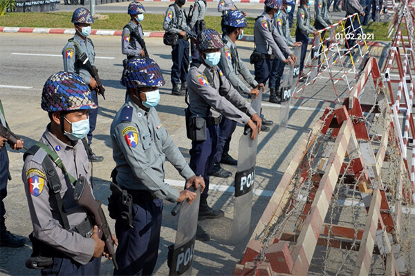 Members of Myanmar police stand by a cordoned off blockade area on the street.