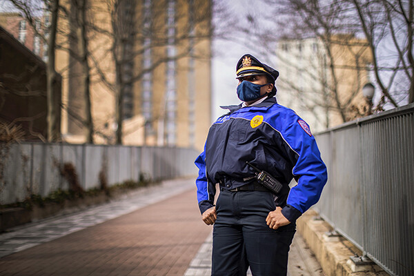 picture of Captain McCoy standing on Penn campus wearing a face covering in police uniform