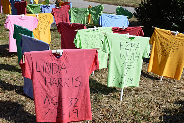 Yard full of standing colorful t-shirts with the names of people killed by guns in black marker written across them.