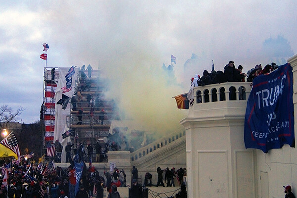 Angry mob on the steps of the U.S. Capitol with tear gas in the air.