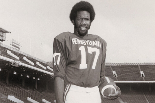 Marty Vaughn standing with a football on Franklin Field in 1974.
