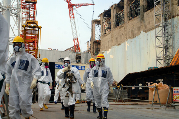 People in hazmat suits walk around the Fukushima nuclear plant in 2013