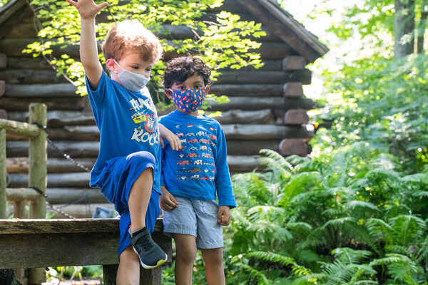 two children wearing masks in front of a log cabin and lush ferns
