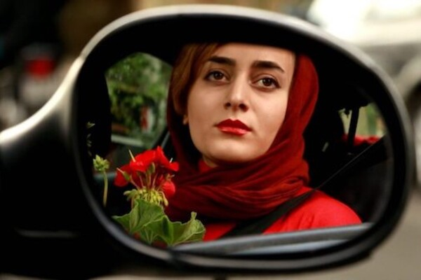 A woman with a red headscarf, red red jacket and red lipstick holding a red geranium is seen in a reflection in a car's side mirror