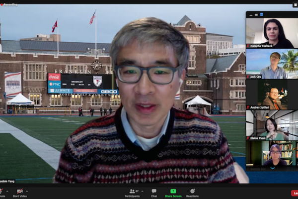 Person wearing glasses speaks on a Zoom call in front of a background featuring Penn's football stadium, as five others on the call are in a vertical column on the right side of the screen