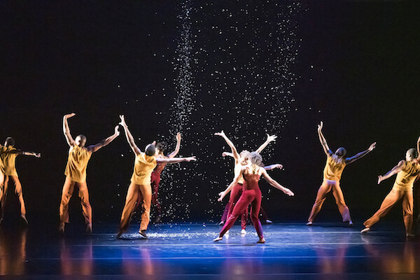 Modern dancers with arms outstretched perform in a spotlight as confetti rains