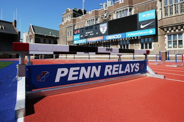 On the track around Franklin Field, a Penn Relays banner rests on the bottom of a hurdle bar.