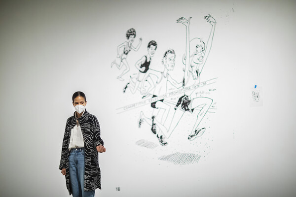 Artist standing in gallery in front of an illustration painted on the wall of people running a race
