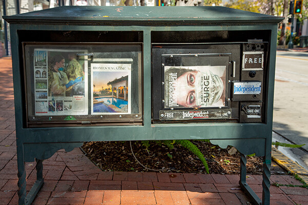 Newsstand featuring three publications, two of which are covid-related.