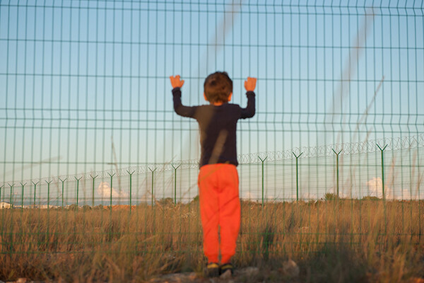 illegal immigration displaced persons camp concept of little boy in black and orange clothes holding fence with barbed wire in desert on state border