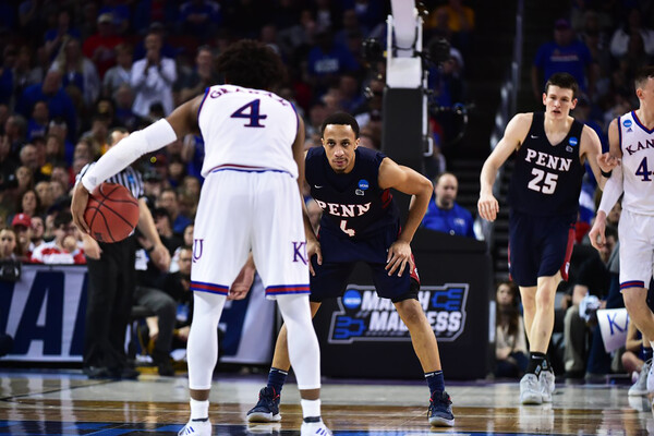 A Penn player defends a Kansas player with the ball at the top of the key during the 2018 NCAA Tournament.