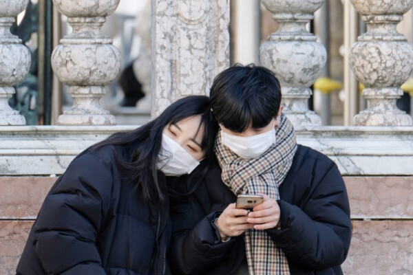 Two people in black jackets wearing white face masks sit in front of marble columns, with the person on the left putting her head on the other person's shoulder, who is looking at a smartphone.