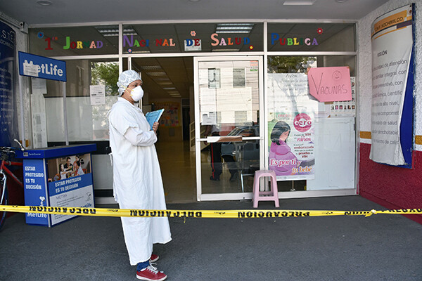 Nurse in a face mask and protective gear stands with a clipboard outside a hospital entrance that is roped off with police tape.