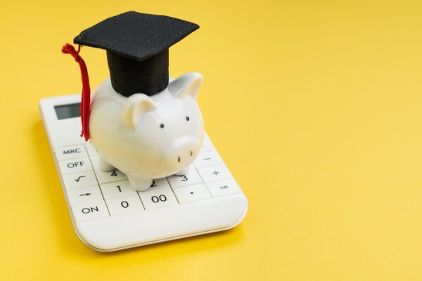 Piggy bank with a graduation cap on top of a pocket calculator.