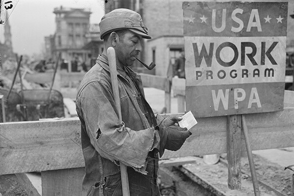 "Man in laborer clothes holds shovel, smokes a pipe and looks at his paycheck by a sign reading ""USA Work Program WPA"""