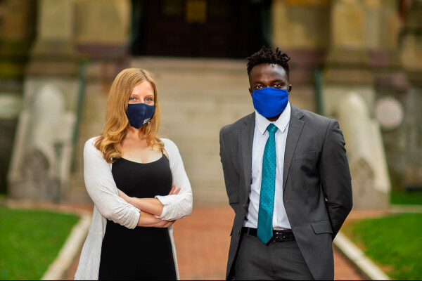 Leah Voytovich and Martin Leet in front of college hall while wearing masks