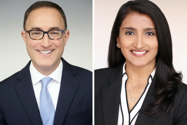 Headshots of two people. On the left is a person with glasses wearing a blazer, white shirt and blue tie. On the right is a person in a black blazer, black-and-white blouse and visible necklace. Both are smiling.