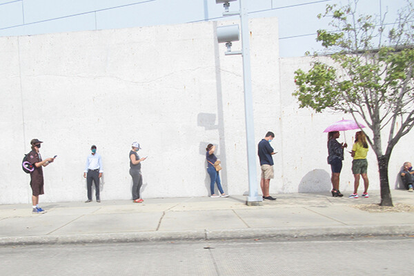 Voters stand in line outside against a white wall, socially distanced and wearing masks.