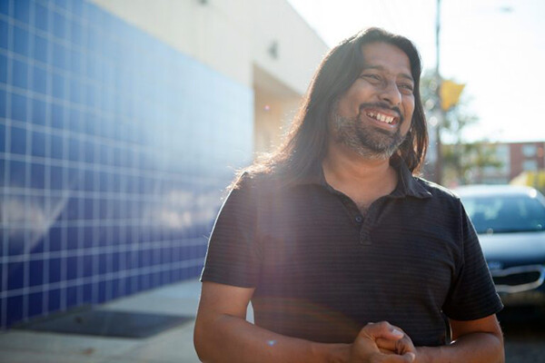 Torju Ghose smiling on a sidewalk in the sunlight.