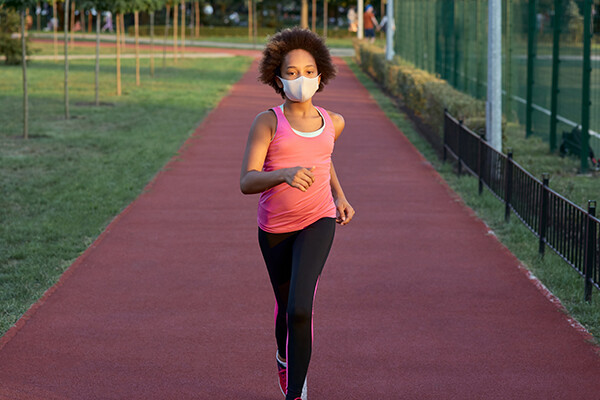 Young person running laps on a track wearing a face mask.