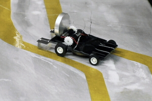 Film still of a small wheeled robot traveling a path between yellow tape.