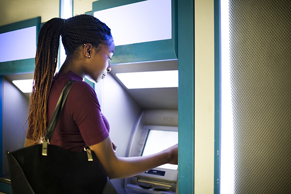 African American woman using an ATM.