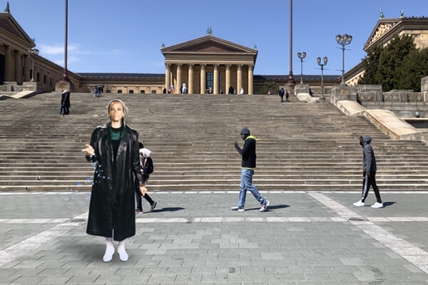 A digital image of Ursula Rucker standing at the base of the Philadelphia Art Museum steps with three people walking behind her.