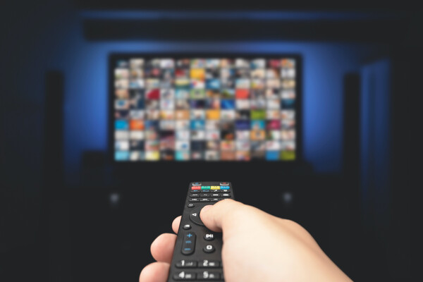A hand holding a television remote, pointed at a blurry TV straight ahead. On the TV are many colored boxes signifying many show options.