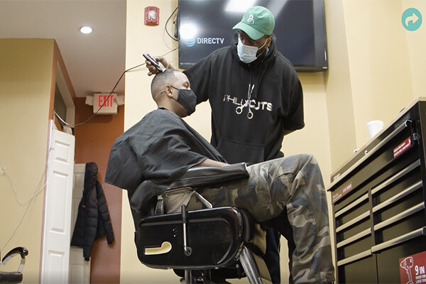 A person wearing a face mask gets their hair buzzed by a barber also wearing a face mask in a West Philly barbershop.