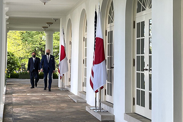 Two men in dark suits and dark face masks walk in the West Wing colonnade at the White House, past two sets of American and Japanese flags