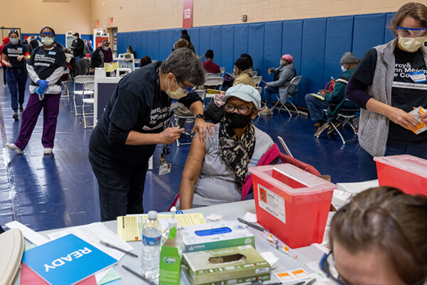 A person receives a vaccination at a Penn Medicine vaccine site by a masked professional while other masked people wait on folding chairs in the room.