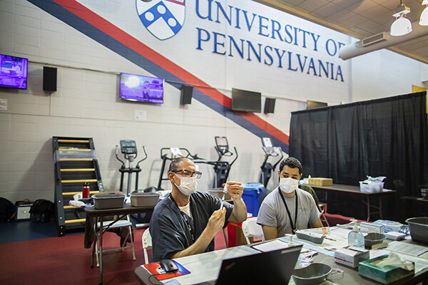 Two people wearing face masks seated at a table, one is preparing a vial of vacccine with a syringe, a University of Pennsylvania shield and logo is on the back wall.