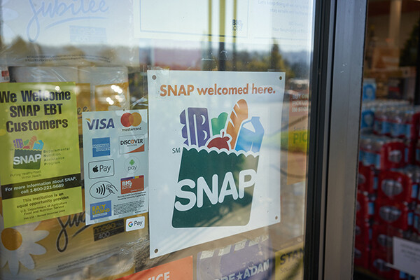 Sign in grocery store windows indicating that SNAP is welcomed there.