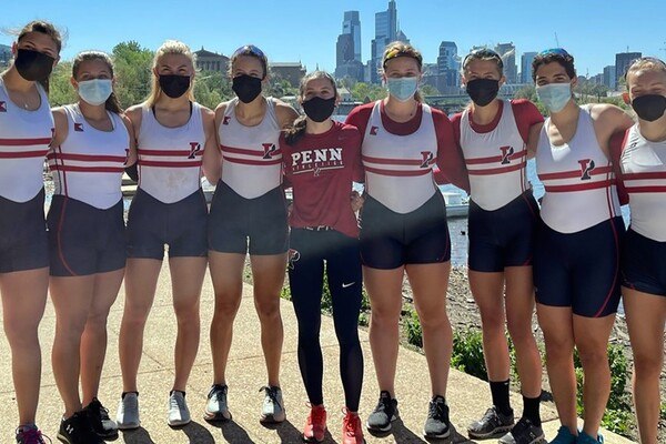 The women's rowing team, wearing masks, poses arm in arm after winning the Kelly Cup on the Schuylkill River.