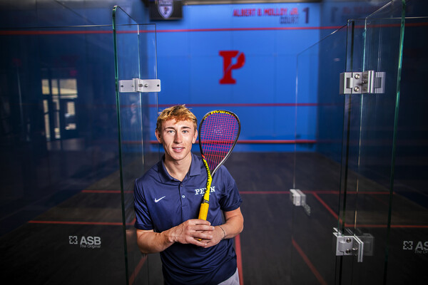 In the doorway of a court at the Penn Squash Center, Andrew Douglas of the men's squash team holds a racquet and wears a blue Penn shirt.