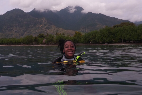 Camille Gaynus in scuba gear in the water with mountains in the background