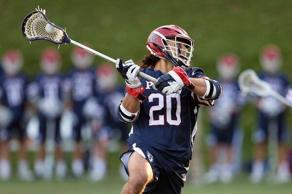 Adam Goldner, wearing his blue Penn jersey, makes a move with his stick with the ball in the net.