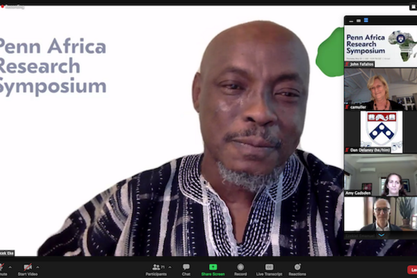 """A Zoom video event shows man in a traditional African print shirt with the words """"Penn Africa Research Symposium"""" on the background behind him, as six participants are seen in video images on the right side of the screen, stacked vertically."""