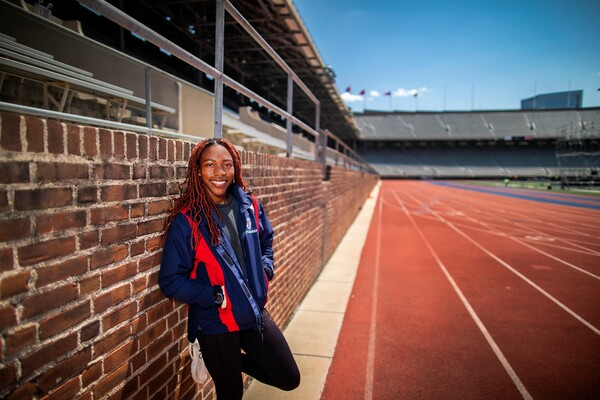 Uchechi Nwogwugwu, wearing a red and blue Penn jacket, leans against a brick wall at Franklin Field, next to the track.