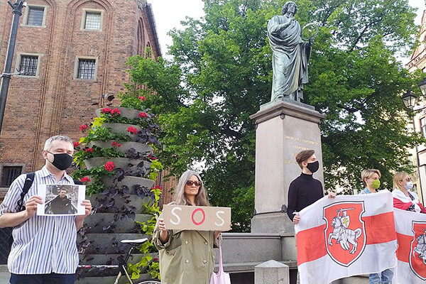 """Six people stand in a square in Poland in front of a statue of a man in toga, some hold Belarusian flags, one woman holds a sign reading """"SOS"""" and a man holds a photo of Belarusian journalist Raman Pratasevich"""