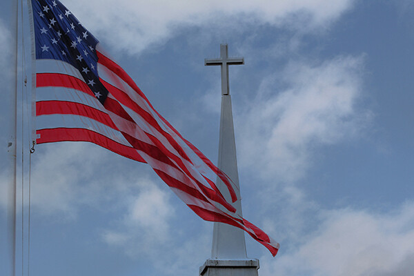 An American flag flaps in front of the tip of a white church steeple topped by a cross, with a blue sky and clouds in the background