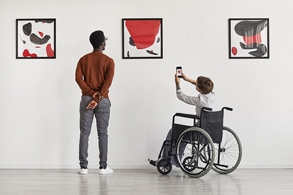 Two people look at three paintings on a wall in a museum, one is in a wheelchair taking a photo with a smartphone.