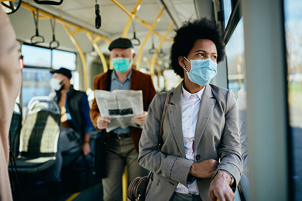 People on a commuter vehicle with face-coverings on