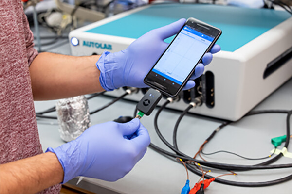 Gloved hands holding a smart phone with a cord plugged in that is attached to lab equipment.