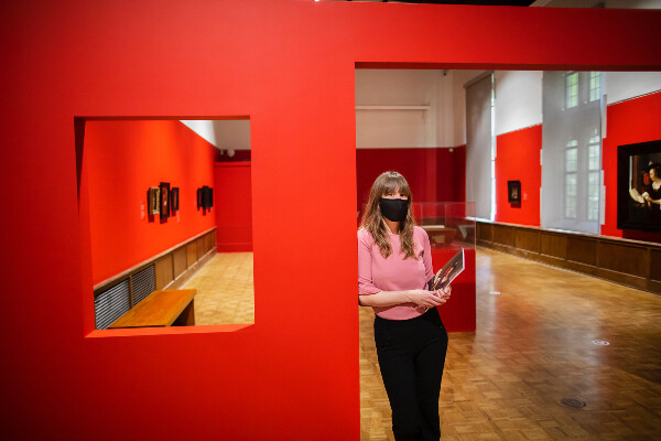 woman standing in doorway of art exhibition with paintings on the walls