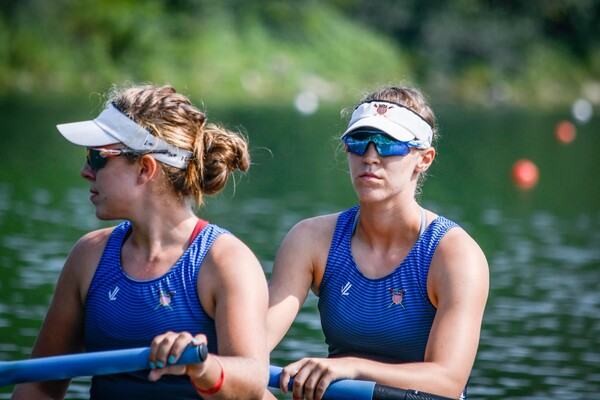 At right, Regina Salmons sits in a boat holding an oar while wearing sunglasses and a blue uniform.