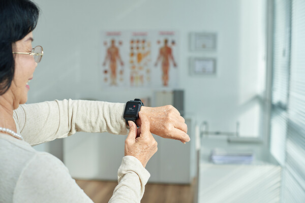 Older person in doctor's office smiling while using a fitness tracker.