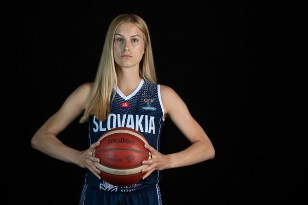 Nikola Kovacikova holds a basketball while wearing her Slovakia women's basketball team uniform, against a black background.