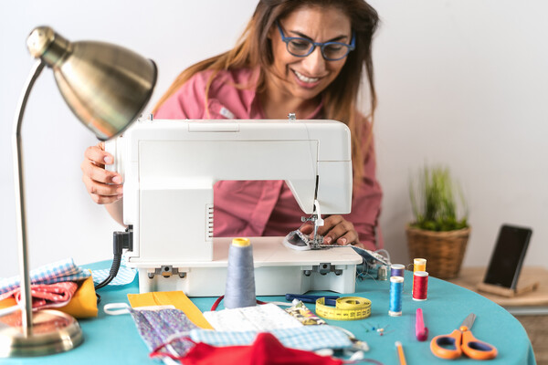 Person smiling at a sewing machine while making masks for COVID-19 face coverings.